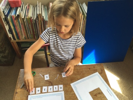 The children take ownership of the investigation by cutting out the numbers themselves before using them to find solutions.